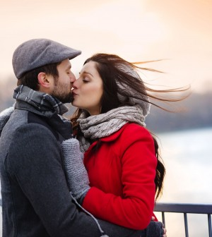32450029 - young couple kissing by the river in winter weather