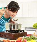 12371491 - young woman is tasting her cooking in the kitchen